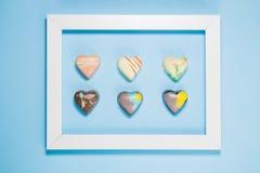 Sześć Belgijskich czekoladowych serc obramiających na błękitnym tle obrazy royalty free