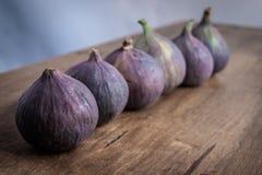 Sześć całych fig wyrównywali z rzędu na drewnianym stole obrazy stock