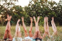 Sześć dziewczyn kłamają na trawie i podnoszą ich nogi up Obrazy Stock