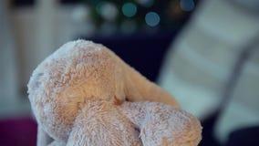 Sześć lat dziewczyn w piżamach bawić się z jej królik zabawką blisko choinki selekcyjnej ostrości zbiory