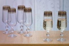 Sześć pięknych szklanych win szkieł, dwa wypełniali z szampanem Zdjęcia Stock