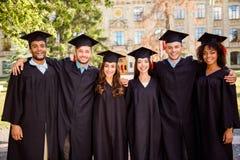 Sześć pomyślnych radosnych wielo- etnicznych atrakcyjnych młodych absolwentów wewnątrz obraz stock