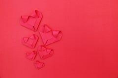 sześć składa czerwieni papierowych serc na czerwieni dla valentine półdupków i wzoru Obrazy Stock