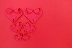 sześć składa czerwieni papierowych serc na czerwieni dla valentine półdupków i wzoru Fotografia Stock