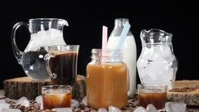 Sześcian lodowy spada puszek w gorącej kawie z jaskrawymi pluśnięciami w zwolnionym tempie Brown temat Foodart strzelał od reklam zdjęcie wideo