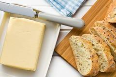 Sześcian masło z pokrojonym chlebem Zdjęcia Stock