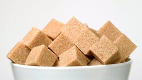 Sześciany brąz trzciny cukier w pucharze wiruje w górę bielu na zbiory