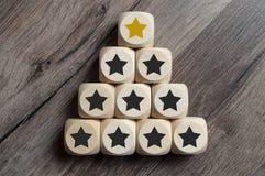 Sześciany i kostki do gry z złotą gwiazdą na górze pyramide zdjęcie royalty free
