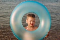 Sześcioletni dziecko utrzymuje dopłynięcie okrąg przy morzem fotografia stock