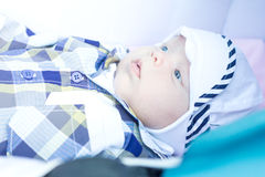 Sześciomiesięczny dziecko kłama w spacerowiczu i spojrzeniach wokoło Fotografia Royalty Free