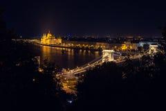 Szechenyi桥梁在布达佩斯匈牙利 美丽的多瑙河 被停泊的晚上端口船视图 图库摄影