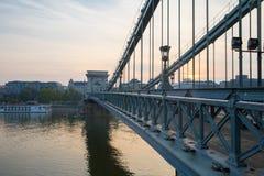 Szechenyi桥梁在布达佩斯匈牙利 美丽的多瑙河 被停泊的晚上端口船视图 免版税库存照片