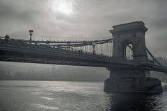 Szechenyi bridge on cloudy day. Szechenyi chain bridge in Budapest against sun breaking through heavy clouds Stock Photos