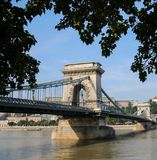 The Szechenyi Chain Bridge , spans the River Danube between Buda and Pest Budapest Hungary. Summer sunny day, blue sky Side view angle , with tree leaves royalty free stock photos