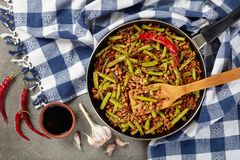 Szechuan Pork Stir Fry with Green Beans. In a skillet on concrete table with soy sauce and dried chili peppers, view from above, close up, flat lay royalty free stock photos