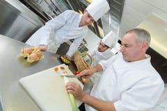 Szefów kuchni asystentom pokazywać dlaczego siekać veggies obraz royalty free