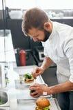 Szefów kuchni Kulinarni hamburgery w kuchni fotografia stock