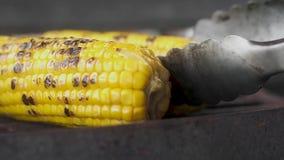 Szefów kuchni tongs obracają smażącą soczystą słodką kukurudzę na grillu zako?czenie, zwolnione tempo zbiory