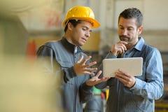 Szef i pracownik sprawdza rezultaty na pastylce obraz stock