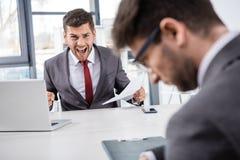 Szef krzyczy przy wzburzonym kolegą przy miejscem pracy z dokumentami zdjęcie stock