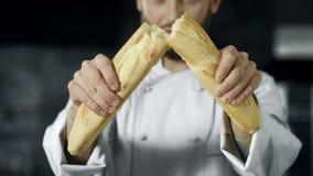 Szef kuchni łama francuskiego chleb w zwolnionym tempie Zbliżenie piekarz wręcza łamanie chleb zbiory wideo