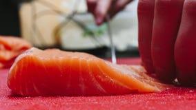 Szef kuchni bierze za kościach od łososia polędwicowego, rozcięcie ryba na plasterkach dla kulinarnego suszi w 4k postanowieniu w zbiory wideo