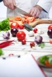 Szef kuchni ciie czerwonego pomidoru jego kuchnia zdjęcia stock