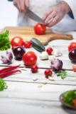 Szef kuchni ciie czerwonego pomidoru jego kuchnia fotografia royalty free