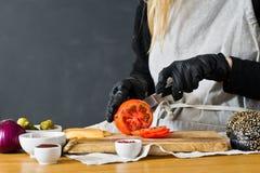 Szef kuchni ciie czerwonych pomidory Poj?cie gotowa? czarnego hamburger Kuchnia, boczny widok, przestrze? dla teksta obraz stock