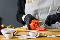 Szef kuchni ciie czerwonych pomidory Poj?cie gotowa? czarnego hamburger Kuchnia, boczny widok, przestrze? dla teksta zdjęcia stock