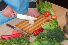 Szef kuchni ciie warzywa w posiłek Przygotowywać naczynia Mężczyzna używa nóż i kucharzów Męski ` s wręcza tnących warzywa obraz royalty free