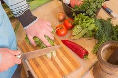 Szef kuchni ciie warzywa w posiłek Przygotowywać naczynia Mężczyzna używa nóż i kucharzów Męski ` s wręcza tnących warzywa zdjęcia royalty free