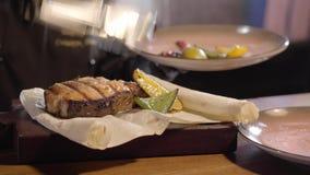 Szef kuchni cytryny i wapna ręka stawiający piec na grillu plasterki blisko dużego kawałka wyśmienicie łosoś ryba na pita używa t zdjęcie wideo