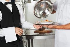 Szef kuchni Daje makaronu naczyniu kelner zdjęcie stock