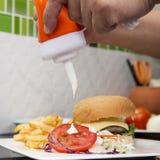 Szef kuchni dekorował hamburger, francuza Freid i jarzynową sałatki, obrazy stock