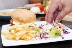 Szef kuchni dekorujący hamburger i francuz Smażący zdjęcie royalty free