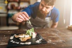 Szef kuchni dekoruje z warzywa naczyniem smażąca ryba Zdjęcia Royalty Free