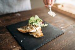 Szef kuchni dekoruje z warzywa naczyniem smażąca ryba Obraz Stock