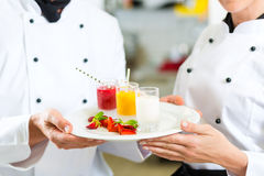 Szef kuchni drużyna w restauracyjnej kuchni z deserem obraz royalty free