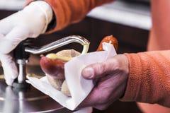 Szef kuchni gniesie out musztardy na tradycyjnej niemieckiej kanapce z mięsnymi kiełbasami Fotografia Royalty Free