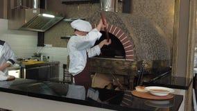 Szef kuchni gotuje pizzę przy restauracją zbiory