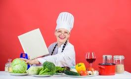 Szef kuchni gotuje zdrowego jedzenie Dziewczyna czytaj?cy ksi??kowi najlepszy kulinarni przepisy Kulinarny szkolny poj?cie Ksi??k zdjęcie royalty free