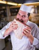 Szef kuchni gryźć surowego mięso na kuchni Zdjęcia Royalty Free