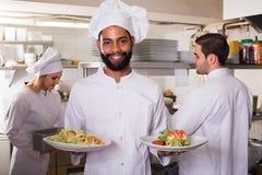 Szef kuchni i jego asystenci przygotowywa posiłek obrazy stock