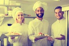 Szef kuchni i jego asystenci przygotowywa posiłek zdjęcia stock