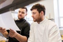 Szef kuchni i kucharz z listami lub rachunkami przy kuchnią fotografia stock