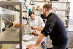 Szef kuchni i kucharz z sklepem spożywczym spisujemy przy kuchnią Zdjęcie Royalty Free