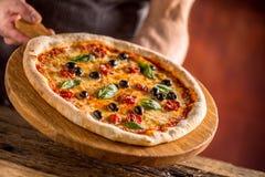 Szef kuchni i pizza Szef kuchni ofiary pizza w hotelu lub restauraci Zdjęcie Royalty Free