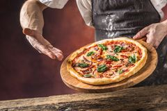 Szef kuchni i pizza Szef kuchni ofiary pizza w hotelu lub restauraci Zdjęcie Stock