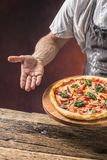 Szef kuchni i pizza Szef kuchni ofiary pizza w hotelu lub restauraci Obraz Stock